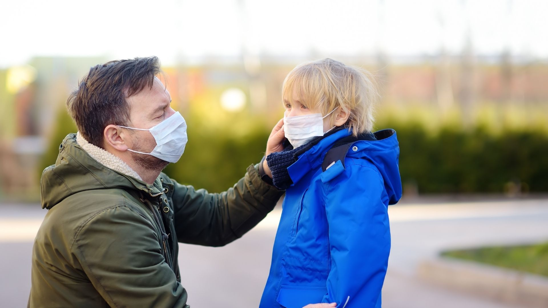 A father with mask on adjusting his child's mask